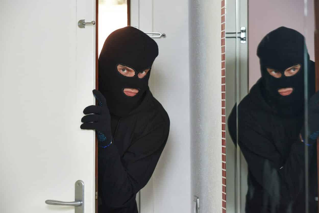 Thief burglar opening door during house breaking penetration
