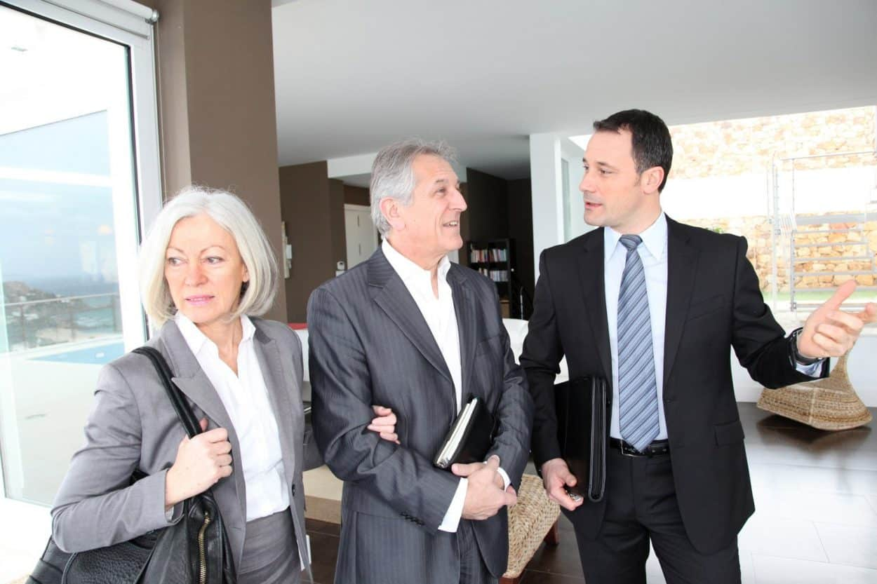 Senior couple visiting modern house with real-estate agent